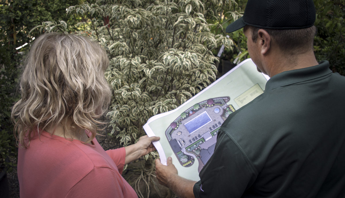 Bealls Landscaping Design Process - Justin going over design plan details and flower selections with a client
